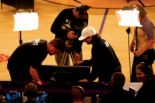 WARM-UPS - 3: Operators test a handheld camera before the game.